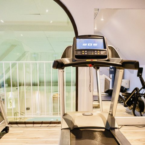A state of the art running machine overlooking a lovely swimming pool