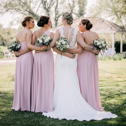 A bridal party posing for photos by the river