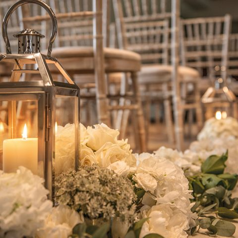 The wedding isle with flowers and a lantern