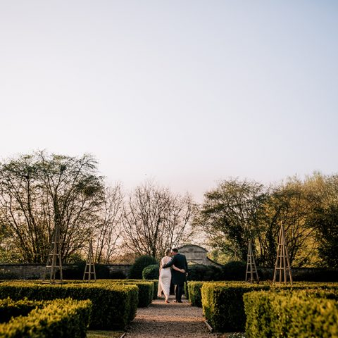 A couple walking through the grounds of Oxford after getting married